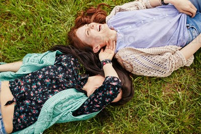 Two cheerful sisters lying on the grass