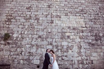 Bride and groom kissing near brick wall