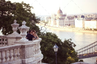 Bride and groom on balcony with cityscape of Budapest