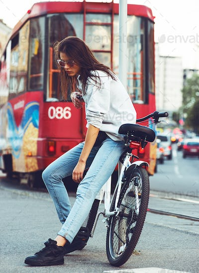 outdoor portrait of young pretty fashion model with bike.