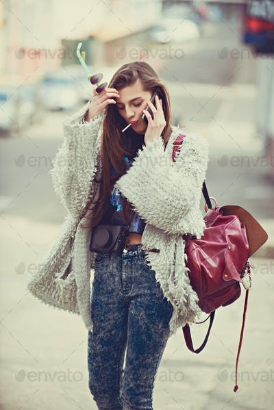 Cheerful woman talking on the phone in the street wearing a gray coat .