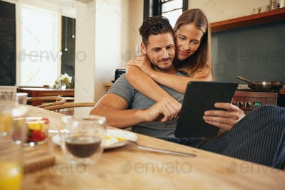Young couple in the kitchen catching up on morning updates