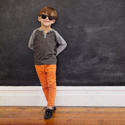 Stylish little boy standing in front of the blackboard