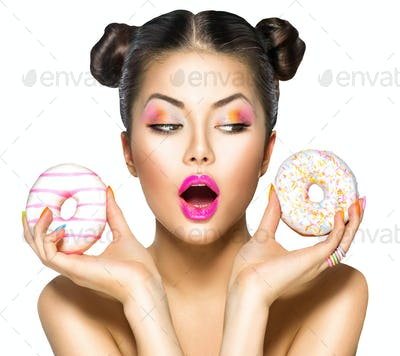 Beauty model girl taking colorful donuts. Dieting concept