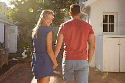 Young caucasian couple walking in the backyard