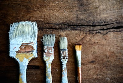 grunge paintbrush on old wood background with copy space