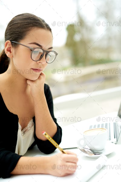 Serious young woman working in the office