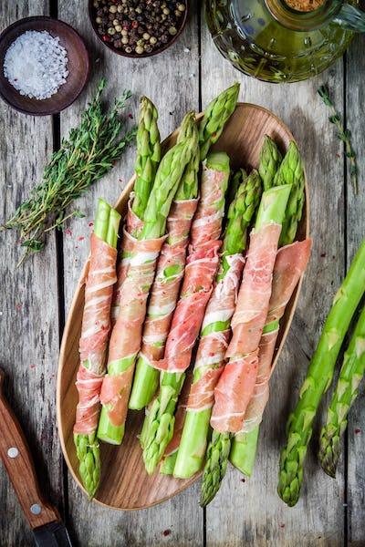 Fresh organic asparagus wrapped in prosciutto on a cutting board