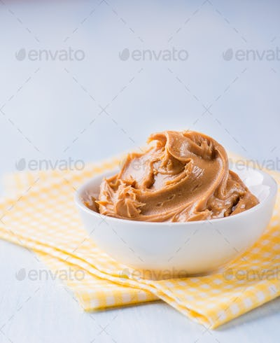 Creamy peanut butter in white bowl