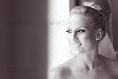 Black and white portrait of a bride near window