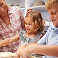Mother preparing pizza with kids