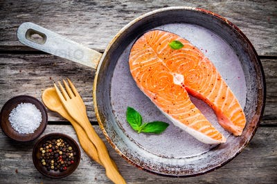 fresh raw salmon steak on cast-iron pan with sea salt and peppers