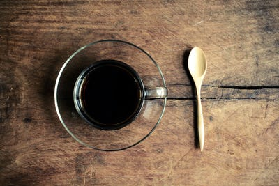 Cup of coffee with wood spoon on old wood textured