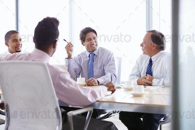 Four Businessmen Having Meeting Around Boardroom Table