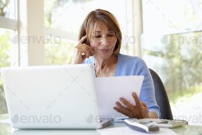 Senior Hispanic Woman Working In Home Office