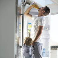 Father And Son Raiding The Fridge For Drink