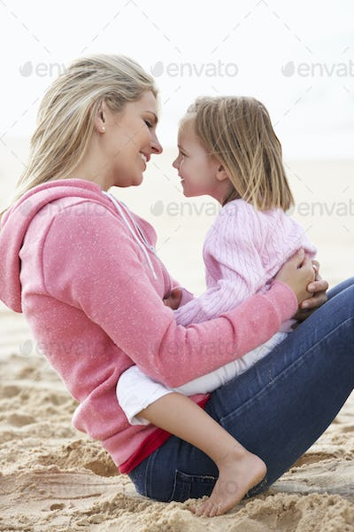 Mother And Daughter Sitting On Beach Together