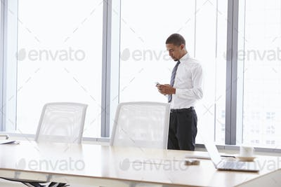 Businessman On Mobile Phone In Boardroom