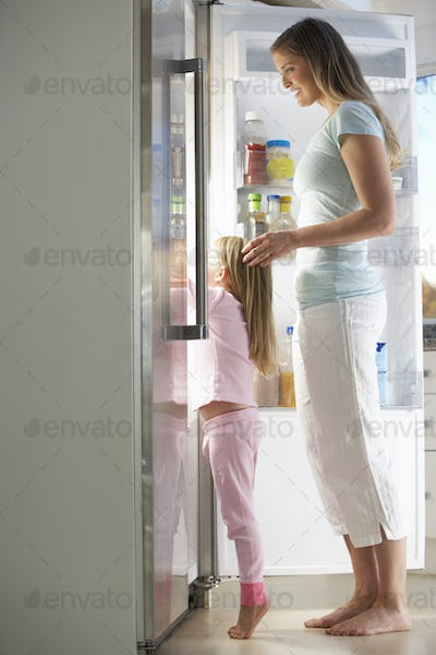 Mother And Daughter Choosing Snack From Fridge