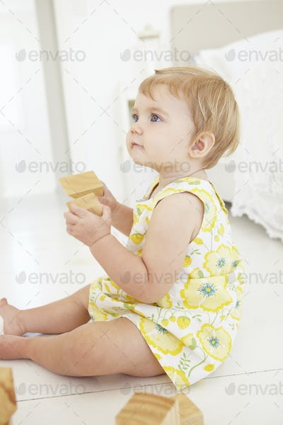 Young Girl Playing With Wooden Building Blocks In Bedroom