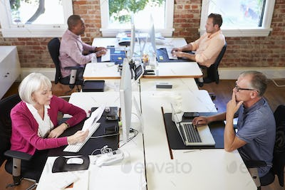 Group Of Workers At Desks In Modern Design Office