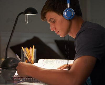 Teenage Boy Listening to Music Whilst Studying At Desk In Bedroom In Evening