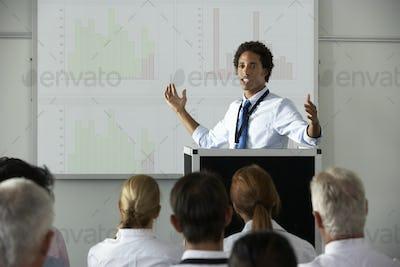 Young Businessman Delivering Presentation At Conference