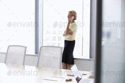 Senior Businesswoman On Mobile Phone In Boardroom