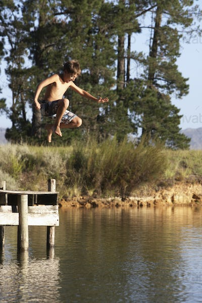 Boy Jumping From Jetty Into Lake