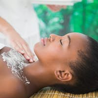 Side view of a pretty woman enjoying a salt scrub massage on the chest