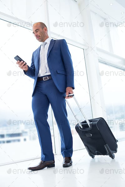 Businessman texting with his smartphone and a suitcase in the office
