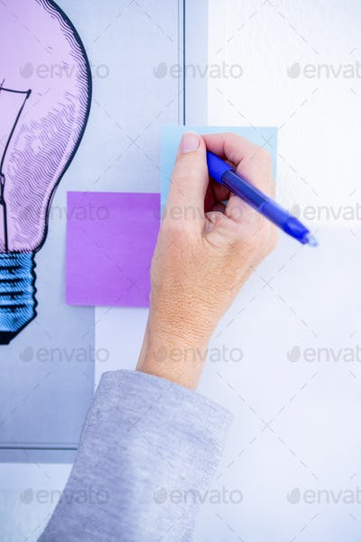 Creative businesswoman writing on post it in office