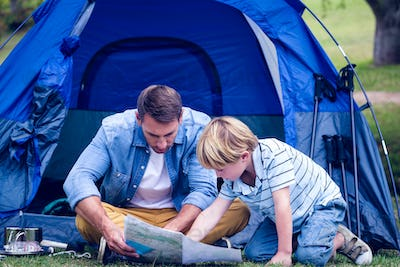Father and son camping in the park on a sunny day