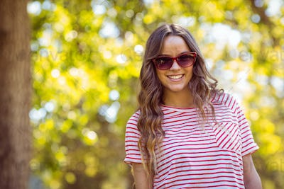 Pretty brunette smiling in the park on a summers day