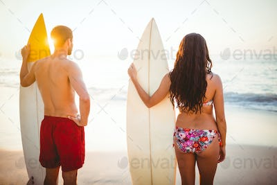 Couple holding surfboards looking at ocean at the beach