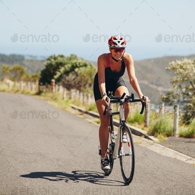 Young woman riding bicycle on open road