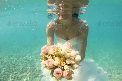 Hands of a bride holding wedding bouquet underwater