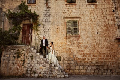 Bride and groom on stairs near a house