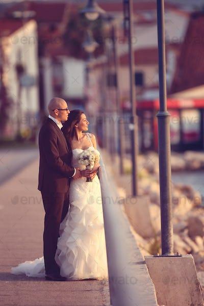 Bride and groom on a bridge near river