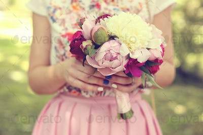 Hands of a woman holding beautiful peonies bouquet