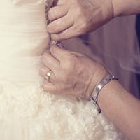 Hands of mother helping the bride with wedding dress