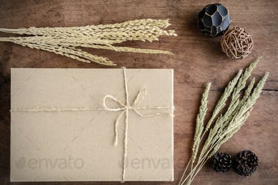 Brown paper box on old wood background with dried flower