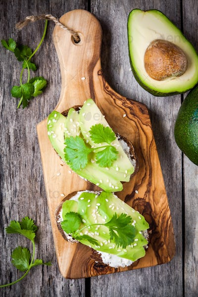 sandwiches with rye bread, sliced avocado, sesame seeds and parsley