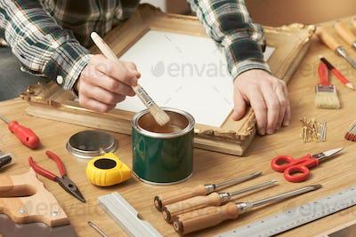 Decorator varnishing a wooden frame