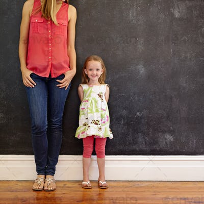 Beautiful little girl standing with her mother smiling