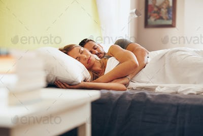 Young couple sleeping peacefully on the bed