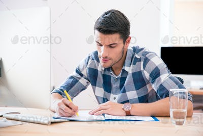 Businessman in casual cloth signing document in office