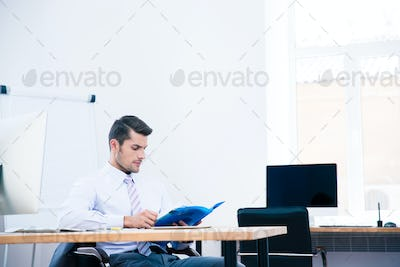 Businessman sitting at the table and reading document