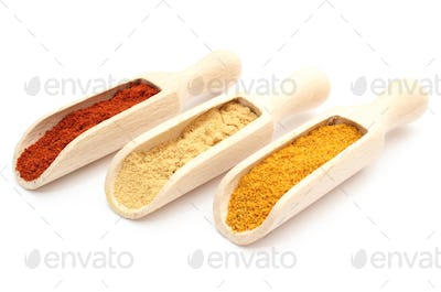 Three spices - curry, ginger and paprika - on wooden spoons