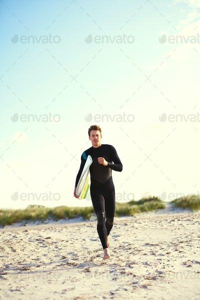 Energetic surfer running across the beach
